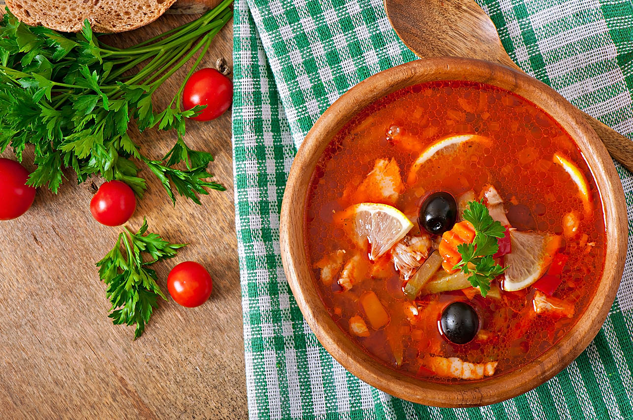 Soup solyanka Russian with meat, olives and gherkins in wooden bowl